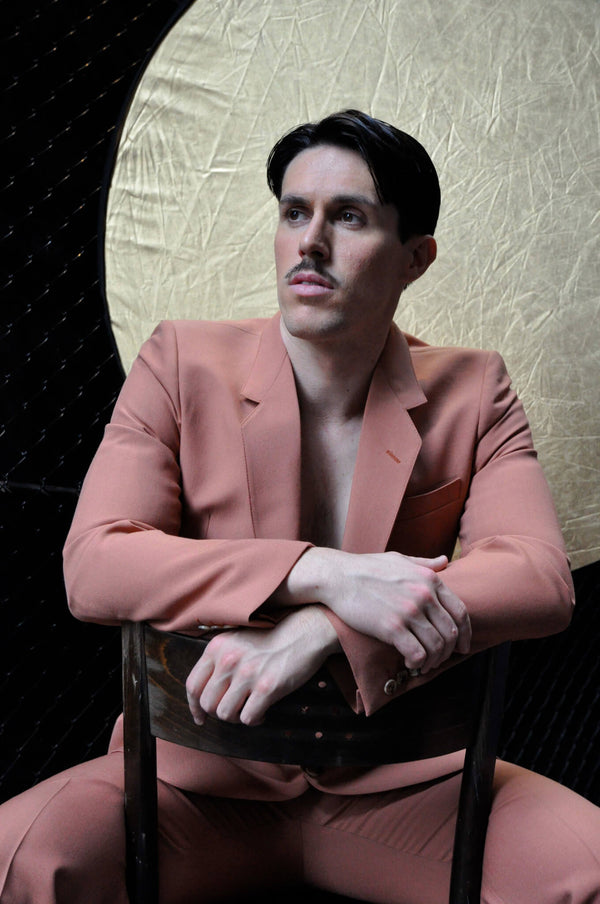 Ross Watson photograph, portrait of Sam Sparro in pink suit sitting backward on chair in front of gold circular backdrop