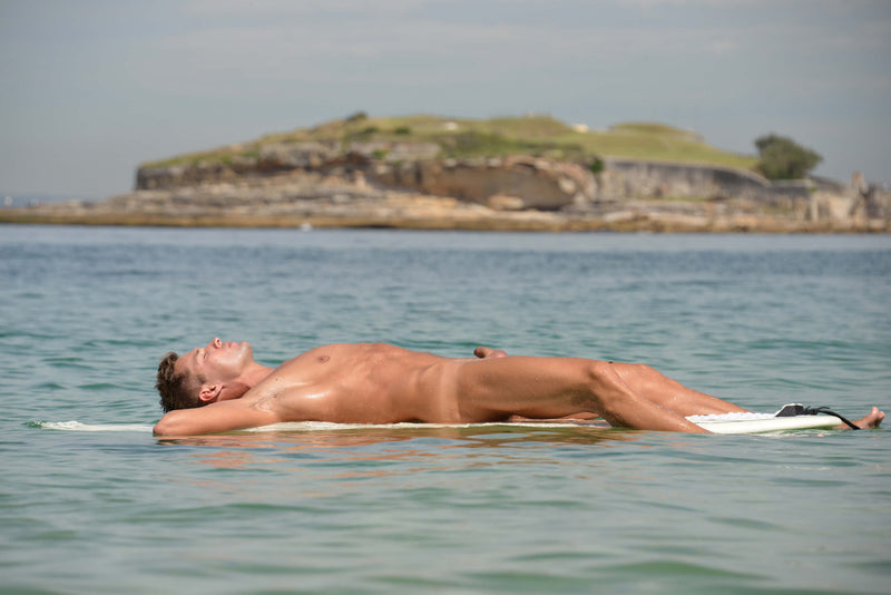Ross Watson photograph of a naked man lying on surfboard in the ocean with an island in the background