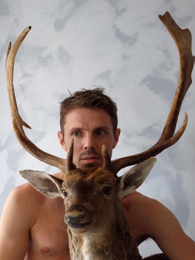 Ross Watson photography of shirtless Jake Shears sitting behind a taxidermy deer head
