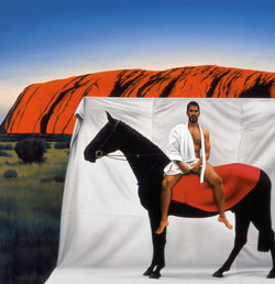 Man wearing martial arts uniform sitting on horse in front of Uluru