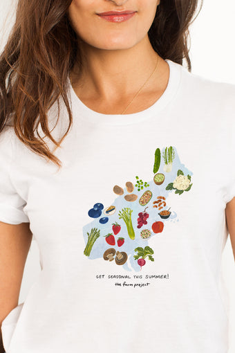 A white t-shirt with a watercolor illustration of seasonal produce in the Northeast