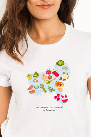 A white t-shirt with a watercolor illustration of seasonal produce in the Southeast