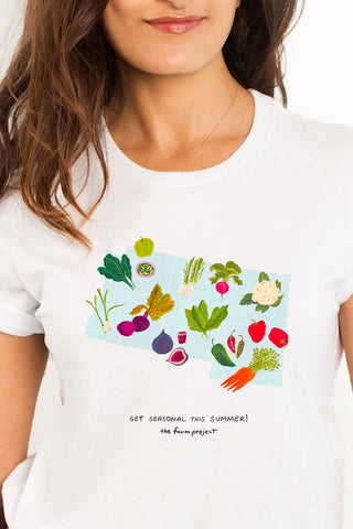 A white t-shirt with a watercolor illustration of seasonal produce in the Northwest