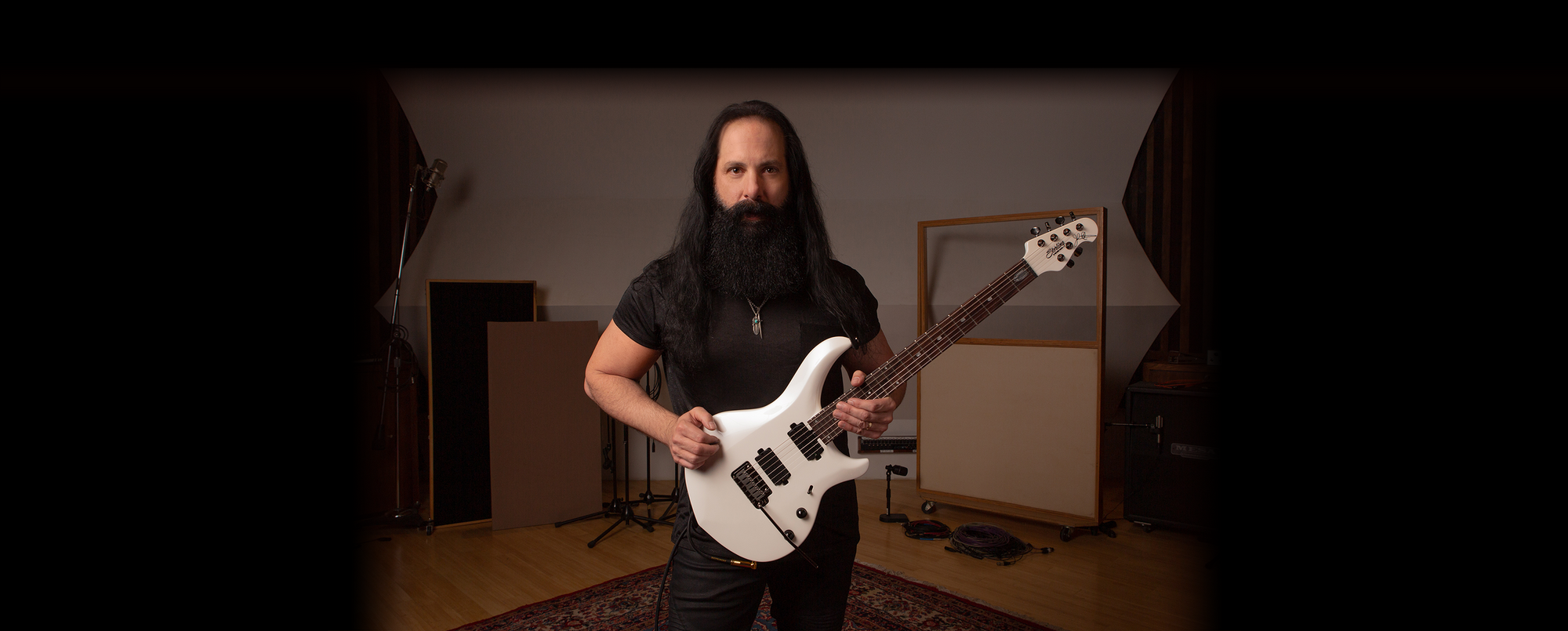 John Petrucci holding the Majesty 7 guitar in Pearl White.