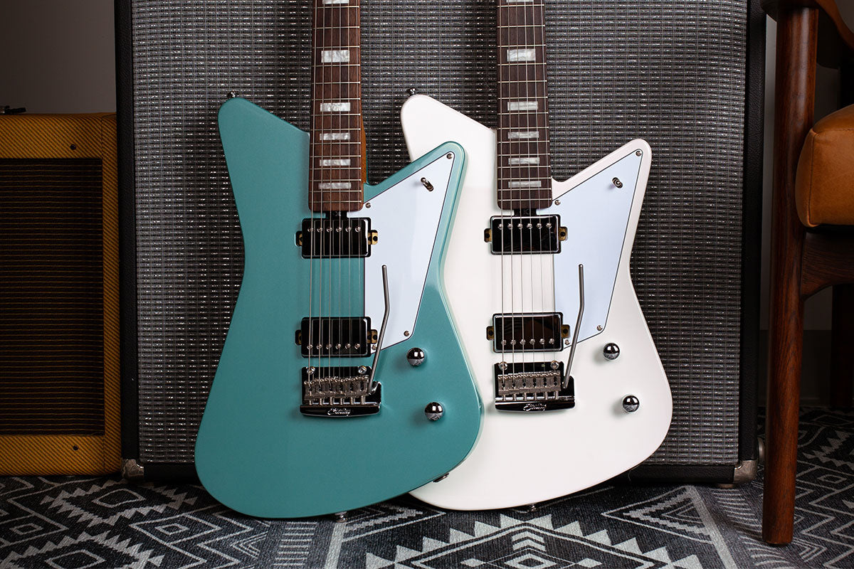 Mariposa guitars in Dorado Green and Imperial White resting against an amp.