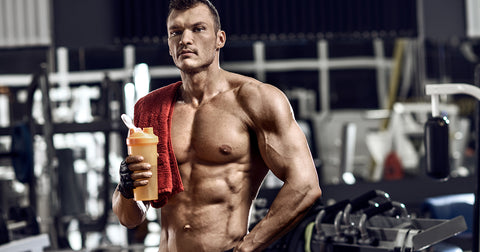 Muscular man holding a protein shaker