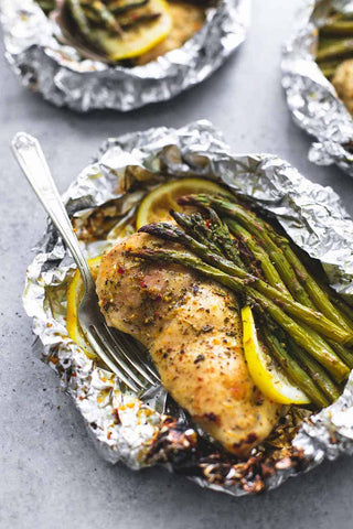 A chicken breast in foil with lemon and asparagus