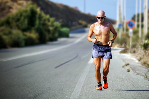 A shirtless man running along the side of a road with green foliage in the background