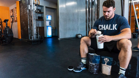A man seated in a gym scooping protein powder into a shaker cup
