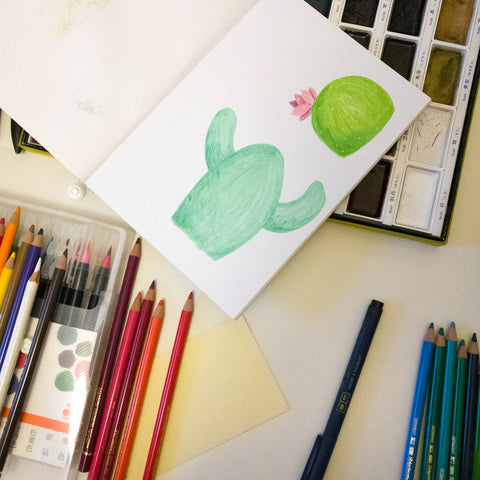 Sketchbook with a cactus illustration and art supplies