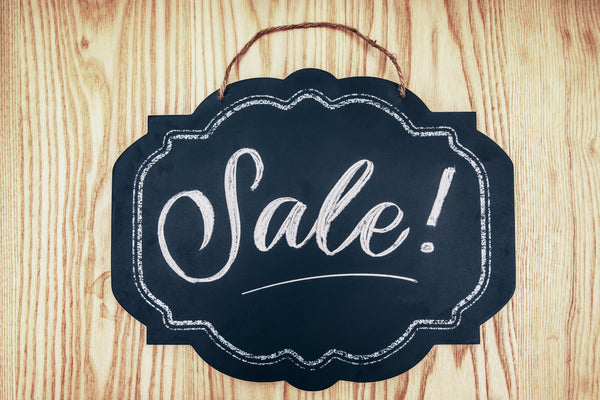 The word Sale written on a chalkboard on top of a wooden background