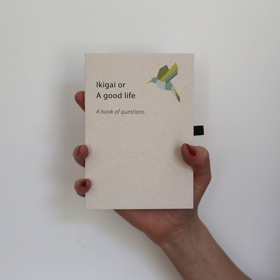 Ikigai or a good life. A book of questions. Cover made of sustainable paper made from leather residues. Favini Remalke Oyster. held in one hand.