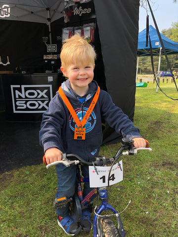 Smiling boy after winning cycle race sitting on his bike and medal around his neck