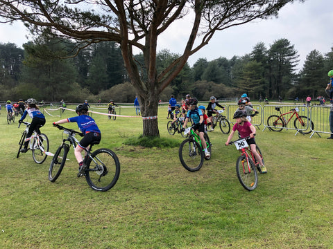 Kids racing around a corner in a Mountain bike race
