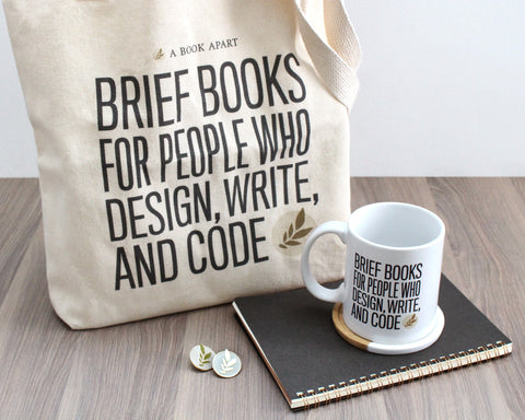 A Book Apart gear, including tote bag, mug, and pins