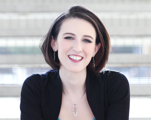 Author Krystal Higgins smiling and wearing a black cardigan and a silver necklace.