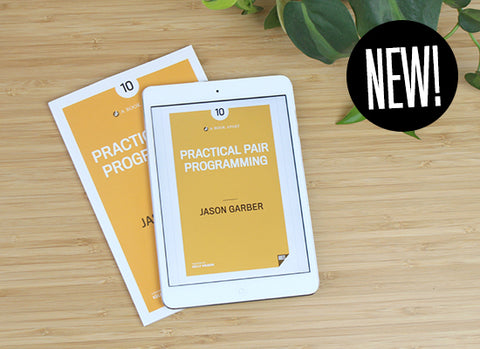 Practical Pair Programming on table in paperback and ebook format.