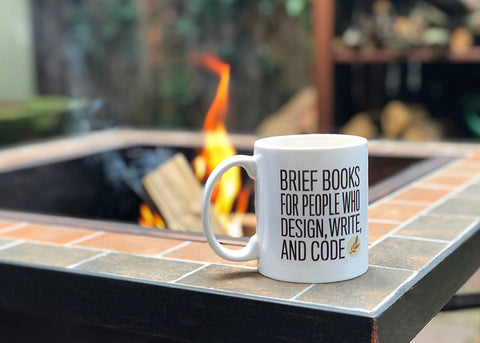 A Book Apart mug in front of an outdoor fire pit.
