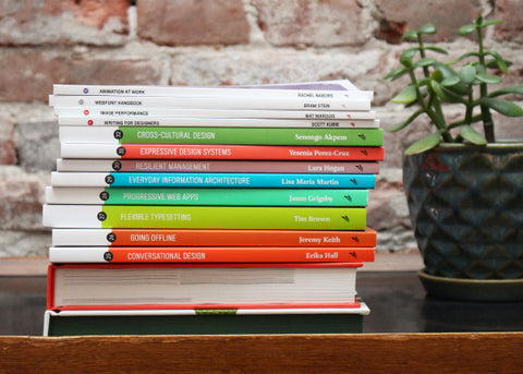 Stack of books next to a green plant, in front of a brick wall.