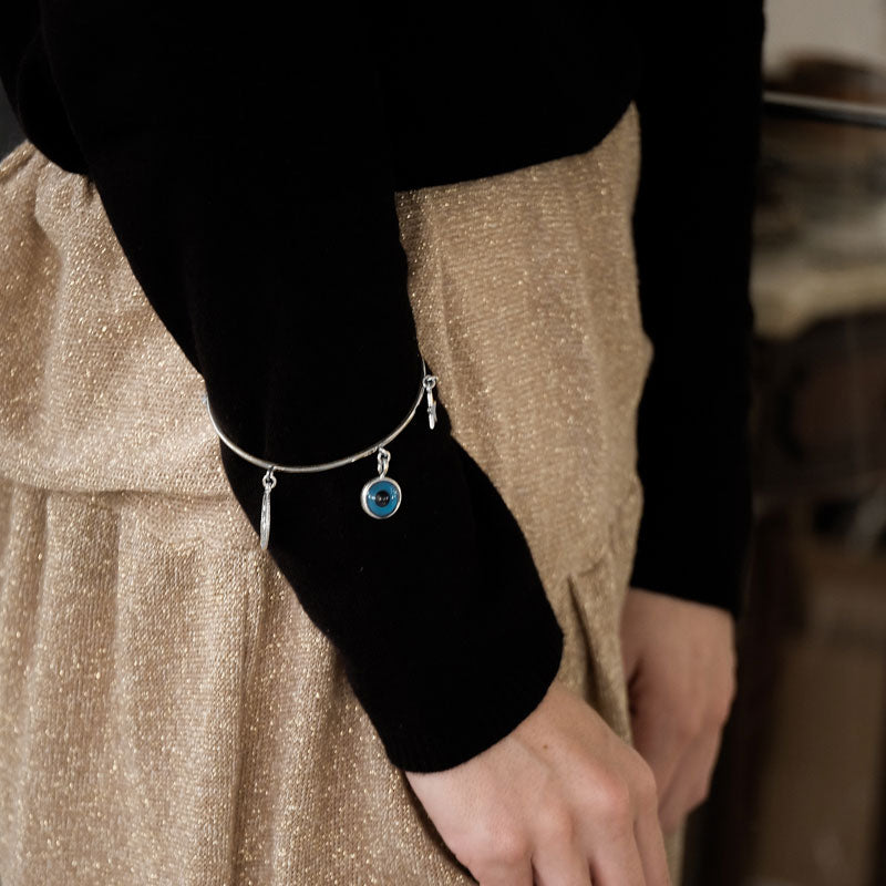 close up of female's right arm. She is wearing a gold skirt and black, long sleeved blouse. Over the blouse, on her forearm, she is wearing a silver charm bracelet
