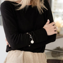 Load image into Gallery viewer, female, in black blouse and gold pants. She is wearing a handmade, silver Santa Maria, talisman bracelet