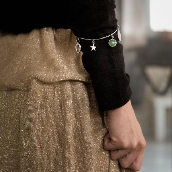 female, in black blouse and gold pants, wearing a handmade, silver Santa Maria, talisman bracelet with green stone by 3rd floor