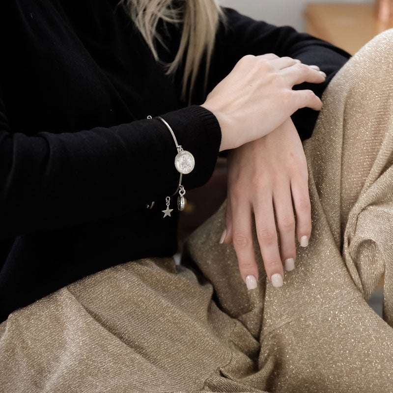 Cropped photo, from shoulders to thighs, of a blond female, in black blouse and gold pants. She is wearing a handmade, silver Santa Maria, talisman bracelet