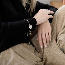 Load image into Gallery viewer, Cropped photo, from shoulders to thighs, of a blond female, in black blouse and gold pants. She is wearing a handmade, silver Santa Maria, talisman bracelet
