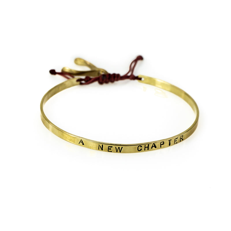Handmade, gold, adjustable bracelet, which ties with a black cord, stamped with the phrase A New Chapter