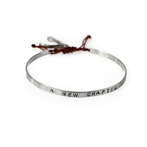 Handmade, silver, adjustable bracelet, which ties with a red cord, stamped with the phrase A New Chapter