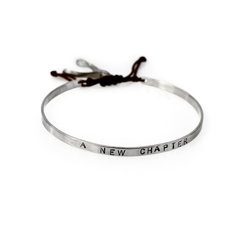 Handmade, silver, adjustable bracelet, which ties with a black cord, stamped with the phrase A New Chapter