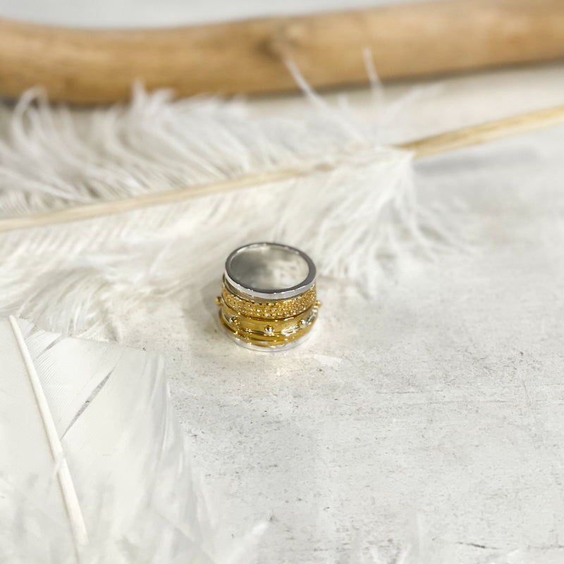 Photo of a wide, silver ring, with additional, gold rings on it. By 3rd Floor Handmade Jewellery