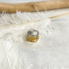 Load image into Gallery viewer, Photo of a wide, silver ring, with additional, gold rings on it. By 3rd Floor Handmade Jewellery