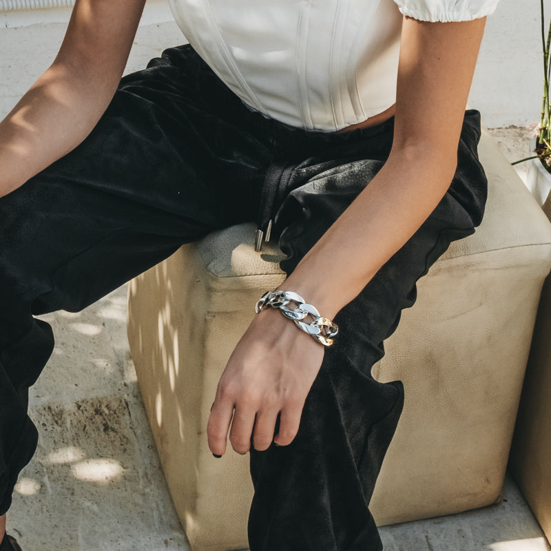 Female in black trousers sitting on a beige stool. On her wrist she is wearing a silver, chunky chain bracelet