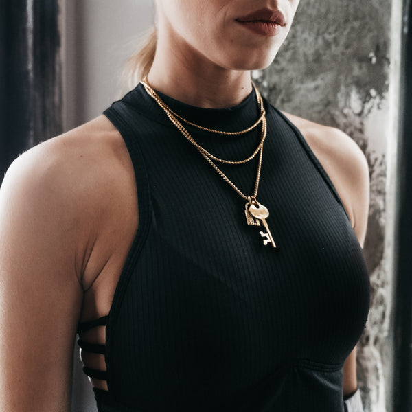 Female in black, off the shoulder blouse. She is wearing a gold, triple chain, lock and key pendant by 3rd Floor Handmade Jewellery