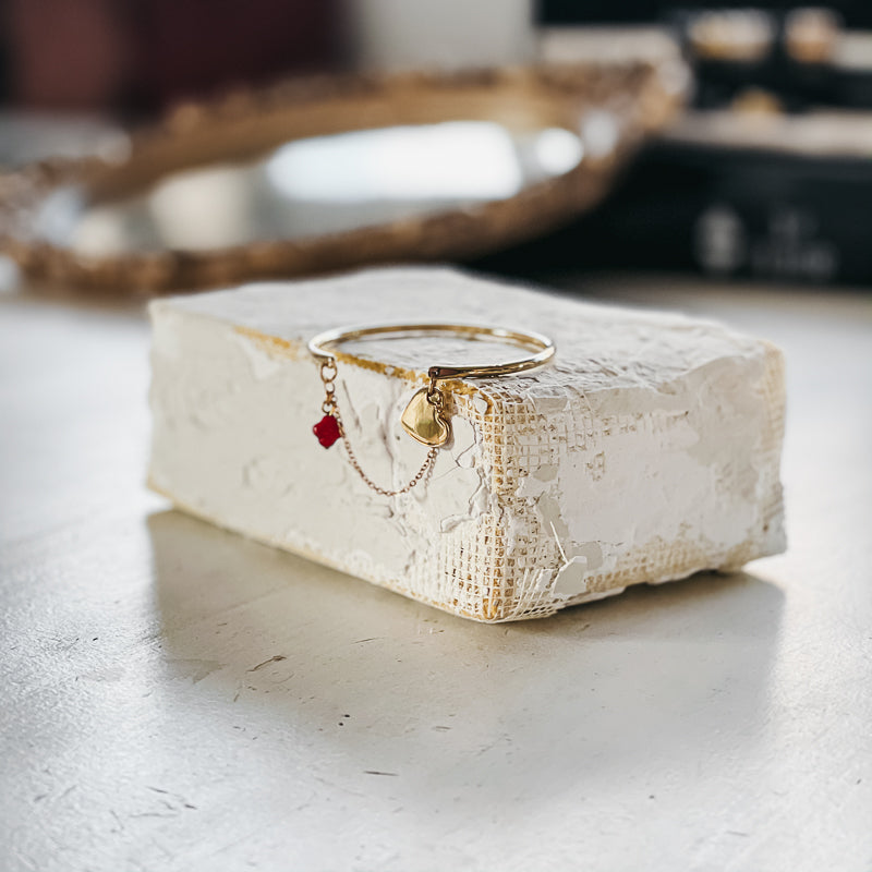 Gold bangle, and chain bracelet, placed on a white, chalk-like brick