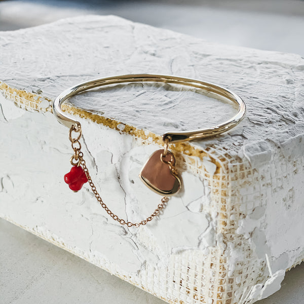 Belamour. Gold, bangle and chain bracelet, with a small, coral cross, and a small heart