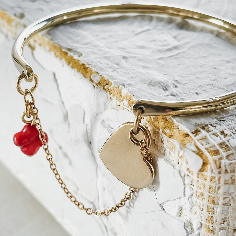 Extreme close up of a gold, bangle and chain bracelet, with a gold heart charm and a small, red coral cross
