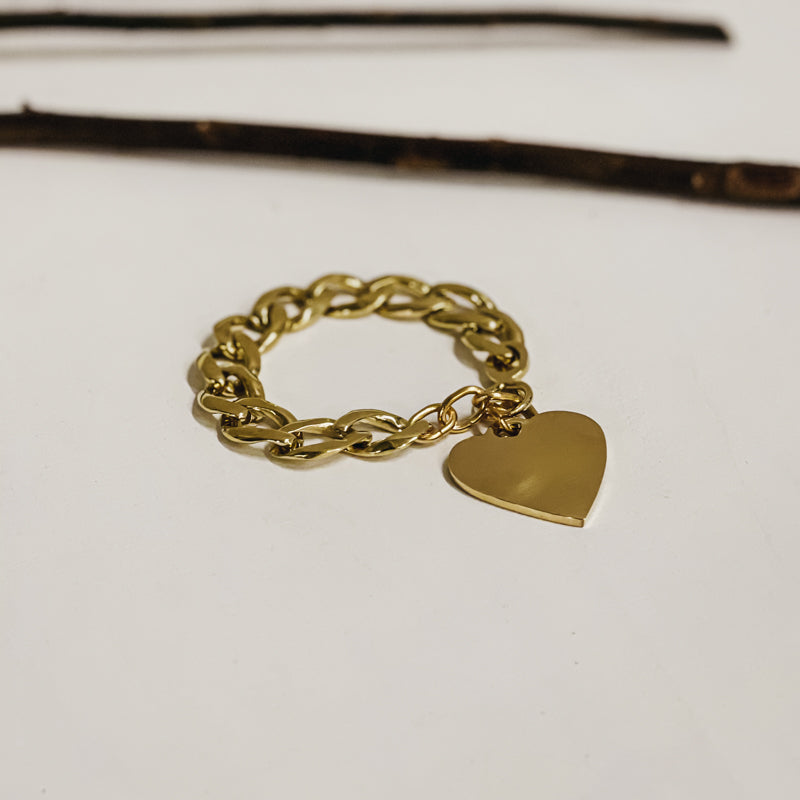 Gold, chunky chain bracelet, with a large, dangling heart, placed on a white table