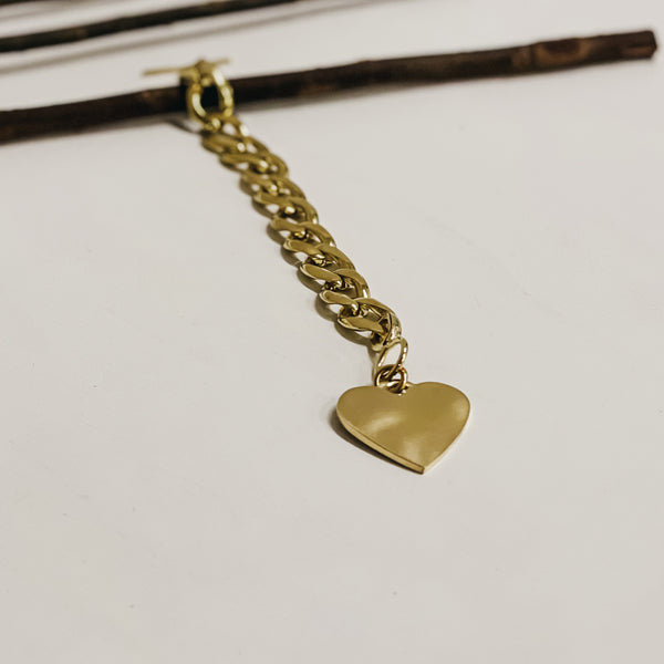 Photo of an unbuttoned, gold, chunky chain bracelet, with a large heart charm