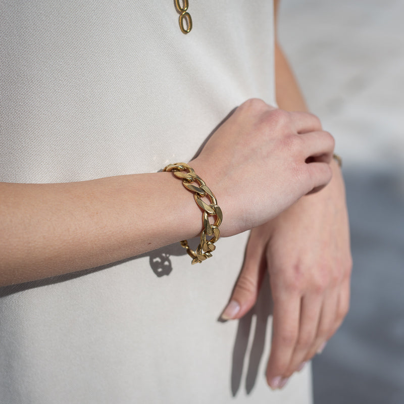 Close up of female's hands. On her left wrist she is wearing a Bilboe, handmade, gold plated brass, bracelet.