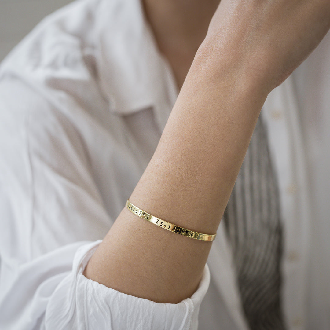 close-up female's arm, with, Gold plated adjustable bracelet stamped with earth's longitude and latitude coordinates