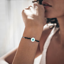 Load image into Gallery viewer, Female wearing a black and grey cord, evil eye bracelet, on her left hand