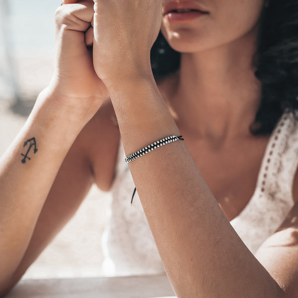 Females hands, forming an upwards pointed V. On her left hand she is wearing a black cord wristlet wtih silver beads