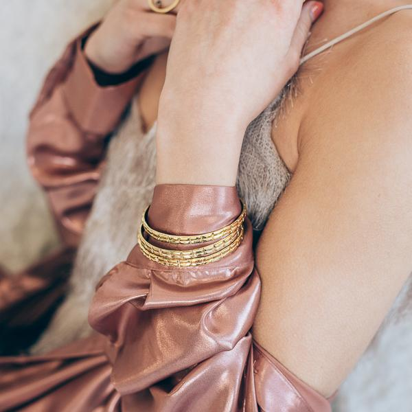 close-up woman in pink, wearing gold handmade bracelets paloma