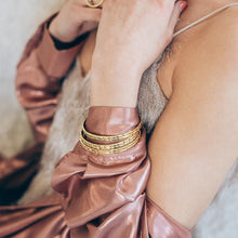 Load image into Gallery viewer, close-up woman in pink, wearing gold handmade bracelets paloma