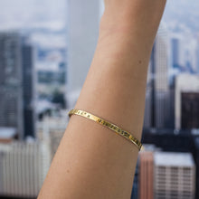 Load image into Gallery viewer, close-up girl's arm, with, Gold plated adjustable bracelet stamped with earth's longitude and latitude coordinates