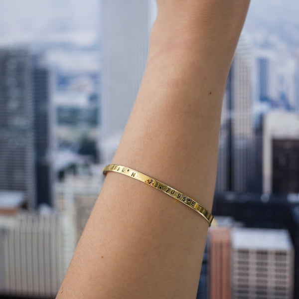 close-up girl's arm, with, Gold plated adjustable bracelet stamped with earth's longitude and latitude coordinates