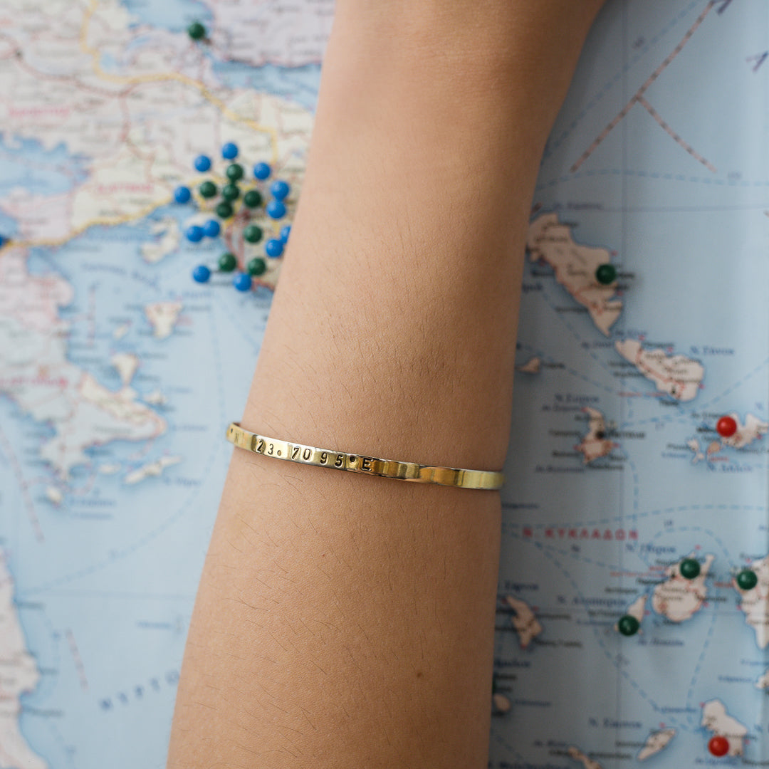 close-up model's arm, with, Gold plated adjustable bracelet stamped with earth's longitude and latitude coordinates