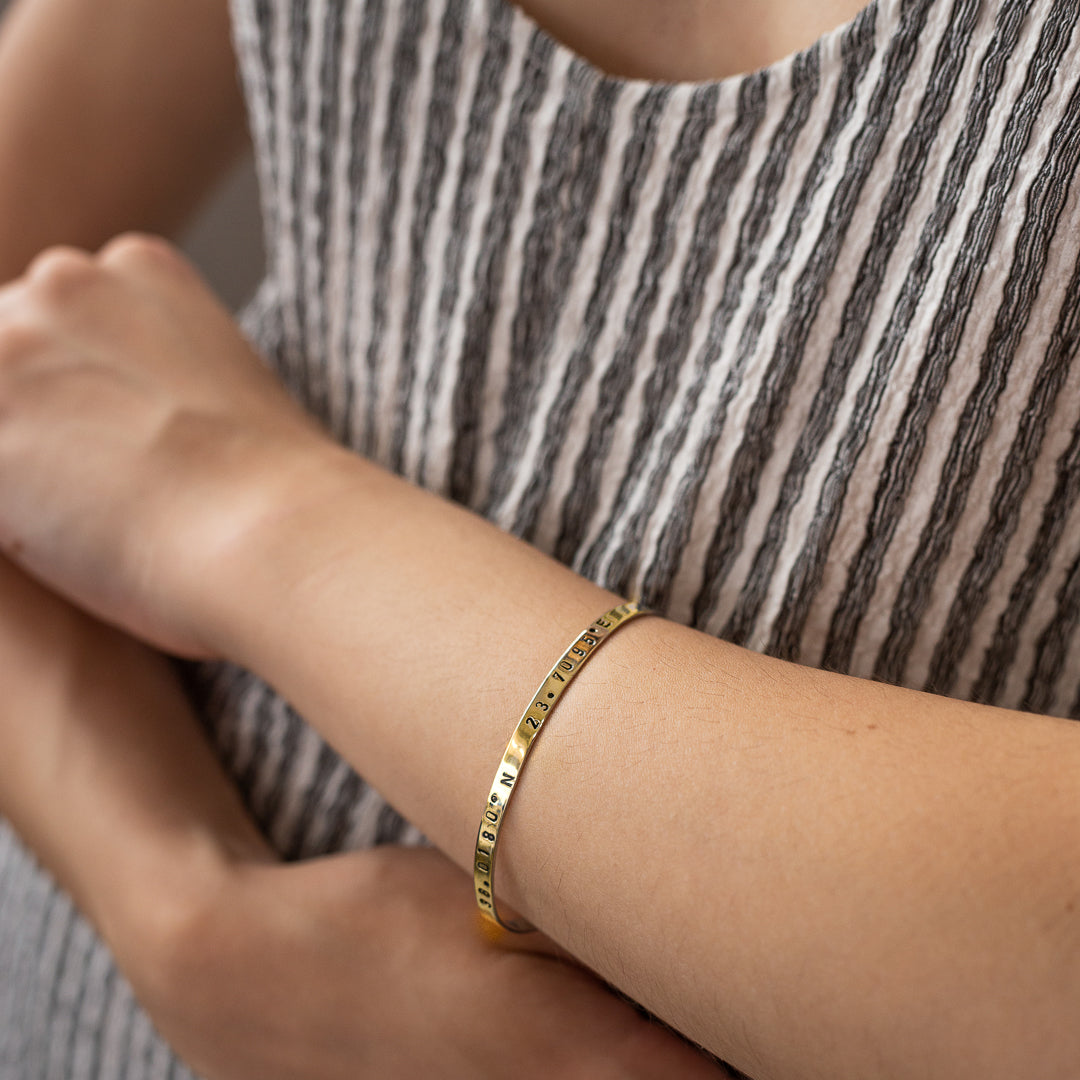 close-up woman's hand, with, Gold plated adjustable bracelet stamped with earth's longitude and latitude coordinates